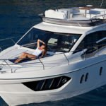Femme allongée sur un bateau au mouillage de type Motoryacht de la marque Absolute, modèle 40 FLY.