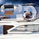 Femme allongée sur une banquette et homme conduisant un bateau de type Motoryacht de la marque Absolute, modèle 40 FLY.