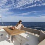 Femme prenant le soleil sur une banquette à l'extérieur d'un bateau de type Motoryacht de la marque Absolute, modèle 45 FLY.