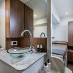 Salle de bain avec lavabo, rangements, donnant sur un lit simple. Bateau de type Motoryacht de la marque Absolute, modèle 52 FLY.
