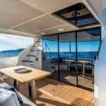 Banquette et table à manger à l'arrière du bateau. Escalier donnant sur l'étage. Bateau de type Motoryacht de la marque Absolute, modèle 58 FLY.