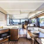 Cuisine équipée, banquette et table à manger, tableau de bord. Bateau de type Motoryacht de la marque Absolute, modèle 58 FLY.