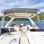 Banquette, tableau de bord et table à manger sur l'extérieur du bateau. Bateau de type Motoryacht de la marque Absolute, modèle 58 FLY.