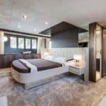 Chambre avec lit double, porte de salle de bain et banquette. Bateau de type Motoryacht de la marque Absolute, modèle 64 FLY.