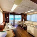 Salon avec banquettes, baies vitrées et buffet. Bateau de type Motoryacht de la marque Absolute, modèle 72 FLY.