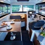 Intérieur comprenant : un tableau de bord, une couchette à l'avant, des coffres de rangement, une table pour manger avec 2 sièges. Bateau de type Fishing de la marque Finnmaster, modèle Pilot 7. Moteur Yamaha.