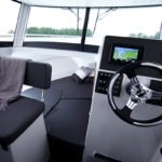 Tableau de bord, volant et couchette à l'avant dans un bateau de type Fishing de la marque Finnmaster, modèle Pilot 7. Moteur Yamaha.