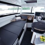 Tableau de bord, volant et couchette à l'avant et longue banquette dans un bateau de type Fishing de la marque Finnmaster, modèle Pilot 7. Moteur Yamaha.