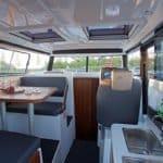 Intérieur comprenant : nombreux hublots, sièges et table pour manger, un espace cuisine, un tableau de bord. Bateau de type Fishing de la marque Finnmaster, modèle Pilot 8. Moteur Yamaha.
