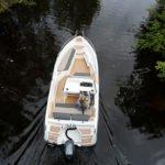 Vue de dessus d'une femme naviguant sur un bateau de type Coque Open de la marque Finnmaster, modèle Consol 52S. Moteur Yamaha.