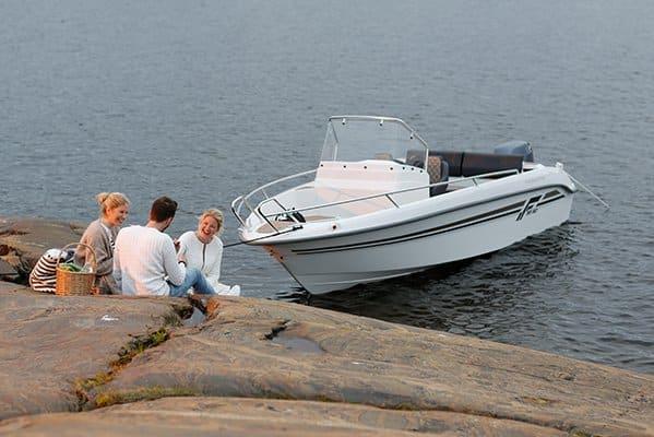 3 personnes pique niquant à côté d'un bateau de type Coque Open de la marque Finnmaster, modèle Consol 55SC. Moteur Yamaha.