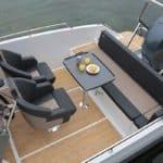 Vue de dessus d'un banquette, d'une table et de sièges d'un bateau de type Coque Open de la marque Finnmaster, modèle Consol 6S. Moteur Yamaha.