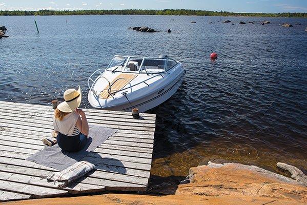 Femme assise sur un quai face à un bateau de type Day-cruiser de la marque Finnmaster, modèle Day Cruiser DC 68. Moteur Yamaha.