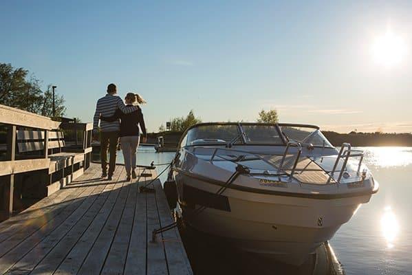Couple se promenant à côté d'un bateau mis à quai, de type Day-cruiser de la marque Finnmaster, modèle Day Cruiser T7. Moteur Yamaha.