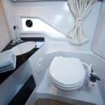 Salle de bain avec lavabo, wc et rangements d'un bateau de type Day-cruiser de la marque Finnmaster, modèle Day Cruiser T8. Moteur Yamaha.