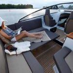 Femme lisant sur une large banquette d'un bateau de type Day-cruiser de la marque Finnmaster, modèle Day Cruiser T8. Moteur Yamaha.