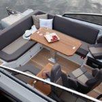 Intérieur comprenant : une banquette, 3 sièges, une table et un tableau de bord. Bateau de type Day-cruiser de la marque Finnmaster, modèle Day Cruiser T8. Moteur Yamaha.