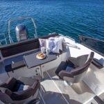 Banquette, chaises et table à manger d'un bateau de type Coque Open de la marque Finnmaster, modèle Husky Aluminium R6. Moteur Yamaha.