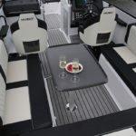 Extérieur comprenant : une large banquette, une table à manger, un tableau de bord avec volant, un siège conducteur et un siège passager. Bateau de type Coque Open de la marque Finnmaster, modèle Husky Aluminium R8S. Moteur Yamaha.