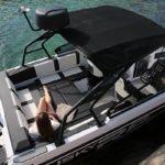 Femme allongée sur une large banquette d'un bateau de type Coque Open de la marque Finnmaster, modèle Husky Aluminium R8S. Moteur Yamaha.