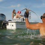 Couple pêchant à la mer à côté d'un bateau équipé d'un moteur Yamaha 115 chevaux.