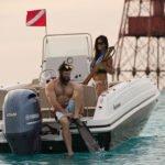 Couple prêt à plonger sur un bateau équipé d'un moteur Yamaha 150 chevaux.