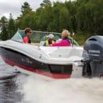 Femme avec deux enfants naviguant sur un bateau équipé d'un moteur Yamaha 150 chevaux.