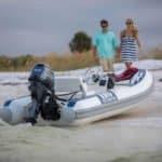 Couple se dirigeant au bord de plage vers un bateau équipé de moteur Yamaha 25 chevaux.